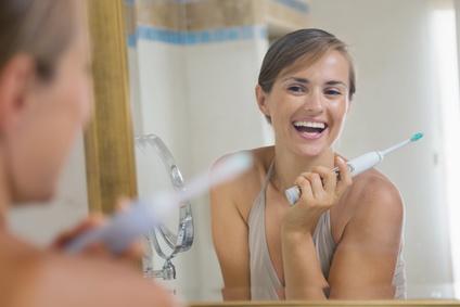 Frau mit elektrischer Zahnbürste